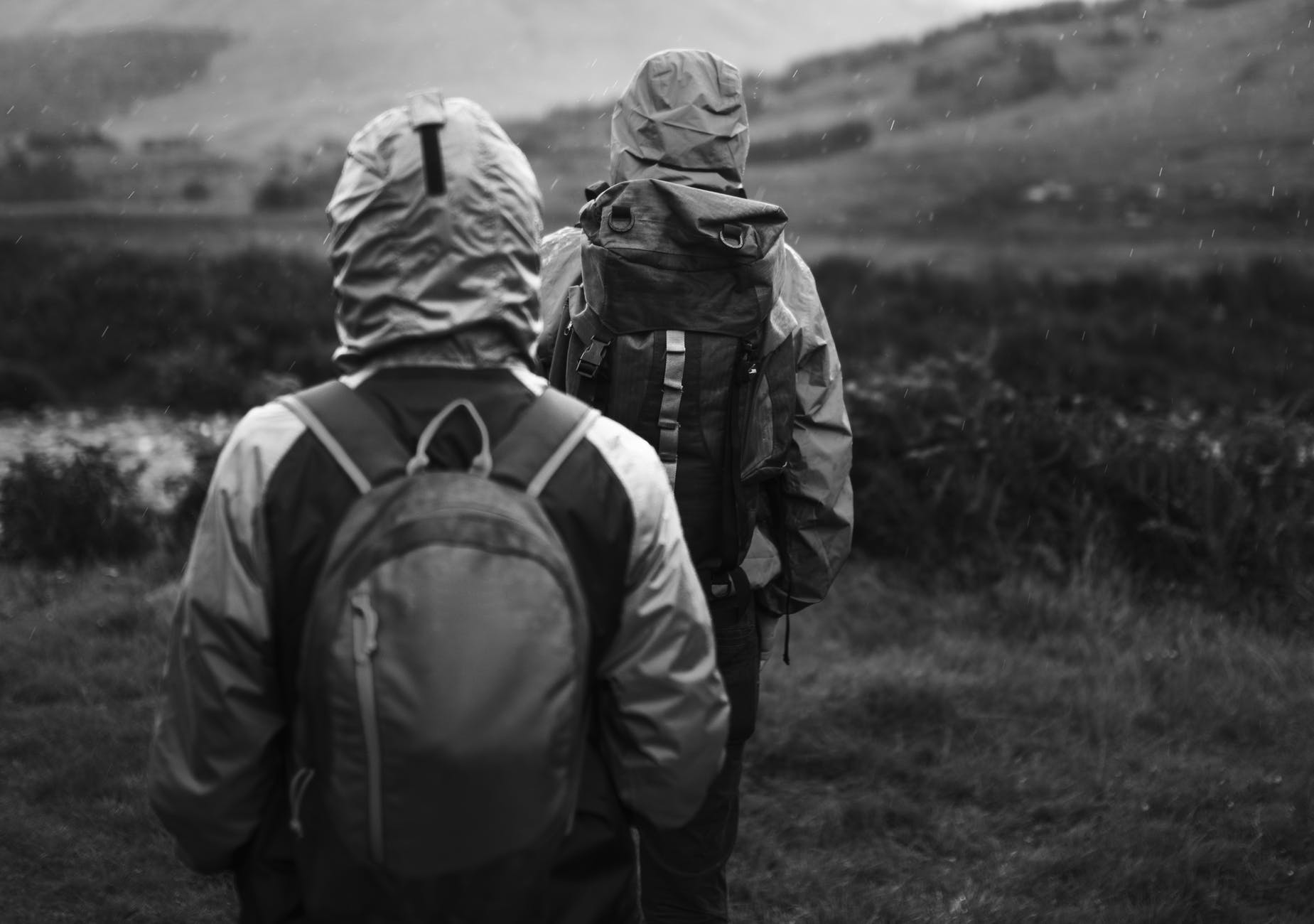 grayscale photo of two hiking backpackers